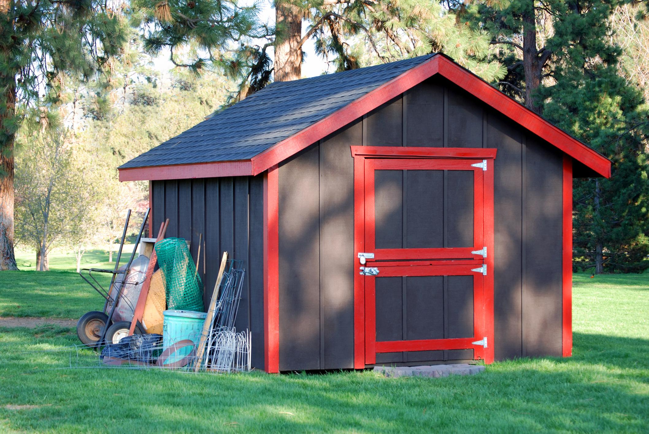 red and black wooden storage shed with metal accents